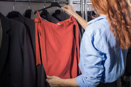 portrait of a beautiful red-haired girl, in a women's clothing store, selects and tries on a skirt from the counter. Sale of women's leather skirts, knitted red skirt, women shop, shopaholic, black sale of women's clothing
