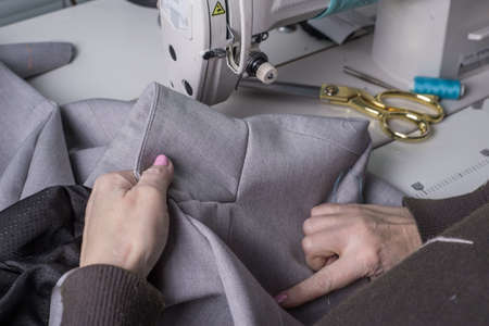 a couturier master, against the background of a sewing machine, sews clothes from high-quality fabric, the manual work of a professional clothing manufacturer. The process of manufacturing a jacket, business suit. Tailoring handmade