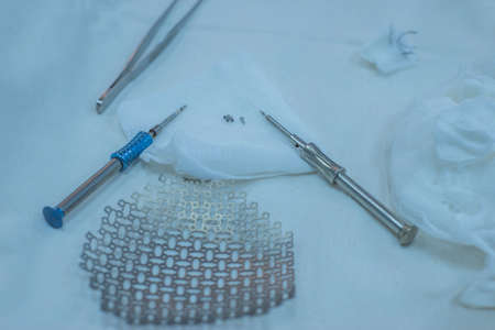 Skull clamp with pins and antiseptic solution for head fixation in neurosurgical surgery operating room neurosurgical instruments, including a titanium plate for implantation in the skull, are on the sterile operating table of a nurse in the operating room.