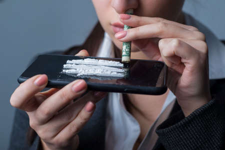 Portrait of a young cocaine girl using coca powder and a straw from a dollar. The problem of drug use in women. Street drug use. Habit, addiction to drugs, evil powders Portret of a young girl, in an office style, business suit. cocaine uses coca powder and rolled up dollar to sniff coca through her nose with a smartphone. Cocaine Tracks