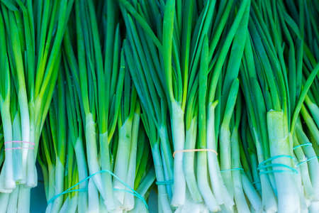 green onion with chives on display closeup green onion texture. Raw greens, vitamin salad. Healthy nutrition, diet food.