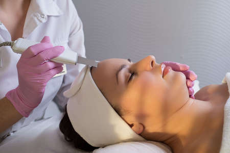 closeup, professional beautician, using an apparatus for ultrasonic face cleaning, cleans the skin of a girl patient, in a beauty salon. Master in cosmetology portrait. Professional and medical facial skin care, when performing procedures that improve facial skin nutrition. Facial skin treatment. Healthy flawless skin. Stock Photo