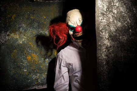 scary clown, in the shadows, looking eerily at the camera from behind an abstract wall. Halloween concept. A very scary clown with a knife in his hand, looks menacingly at the camera, against a dark abstract background. Halloween clown, killer, horror movie Zdjęcie Seryjne