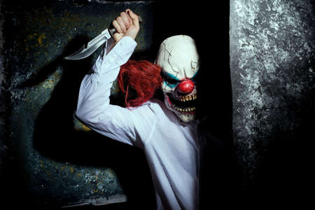 scary clown, in the shadows, looking eerily at the camera from behind an abstract wall. Halloween concept. A very scary clown with a knife in his hand, looks menacingly at the camera, against a dark abstract background. Halloween clown, killer, horror movie