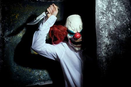 clown effrayant, dans l'ombre, regardant étrangement la caméra derrière un mur abstrait. Notion d'Halloween. Un clown très effrayant avec un couteau à la main, regarde la caméra d'un air menaçant, sur un fond abstrait sombre. Clown d'Halloween, tueur, film d'horreur