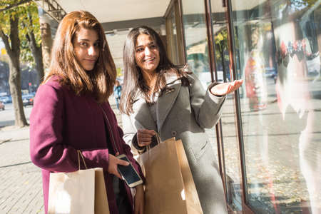two beautiful young girlfriends, of Indian appearance. Girls stand at the window with things, smiling, pointing a finger at the goods. Buying new things, joys. Young beautiful indian girls shopping
