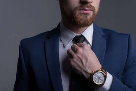 portrait of a young bearded handsome guy in a business suit, looking at the camera, demonstrating a wristwatch, with a leather strap. Advertising mens watches. On a gray background. Business man portrait