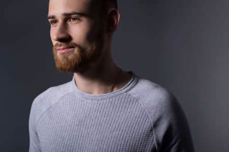 closeup, dramatic portrait of a handsome bearded guy of twenty-five years old, in a gray sweater, on a gray background. Casual style. Sweater, mens jacket. Smiling bearded young guy. Dark colored man portrait