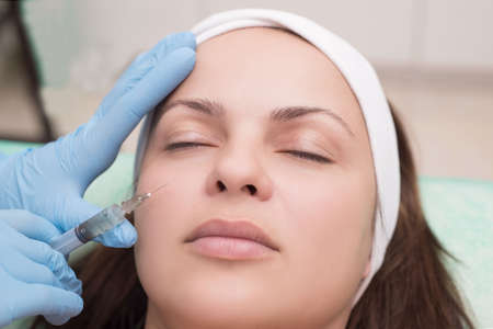 injection into the skin of the face of a young woman, close-up. Beautician with a syringe with a needle introduces a remedy for wrinkles on the face. Fighting the early aging of facial skin in women Stock Photo