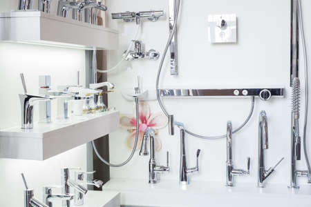 a variety of faucets taps on a white shelf in a shop counter. Close-up of faucets for faucet sink, washbasin. Sanitary engineering shop