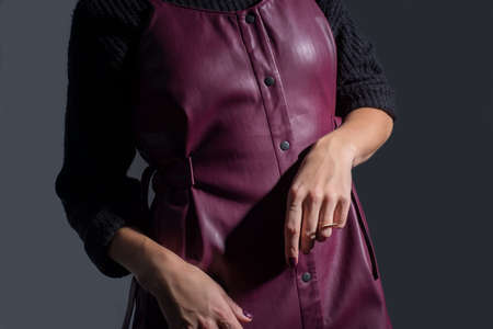 Catalog of advertising photos of a young red-haired girl in a burgundy leather sundress made of quality leather and a black sweater. On a dark gray background. Style and fashion. Women's leather sundresses in red burgund Foto de archivo