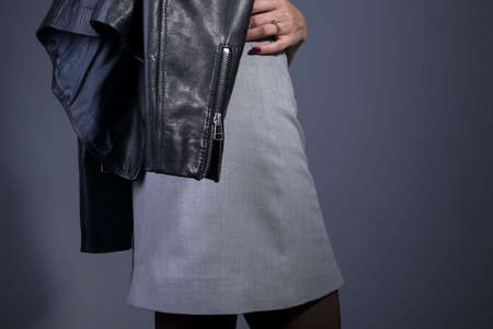 In the catalog of photo advertising, the model is dressed in a gray skirt and a leather jacket in the style of rock and roll, close-up. On a gray background. Catalog for an advertising magazine. High quality leather jacket. Gray designer skirt.