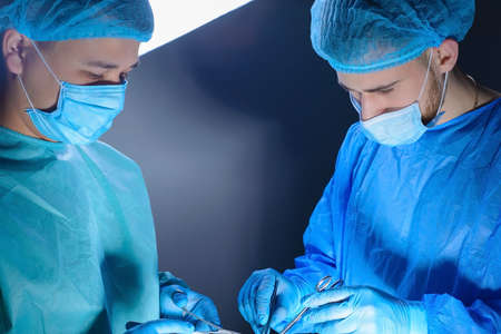 close-up portrait of two surgeons operating in an operating room with instruments. In sterile medical surgical special clothing and masks. Surgery of internal organs, reconstructive and plastic surgery. Medical concept of minimalism Reklamní fotografie
