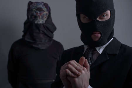 Close-up studio portrait, two robbers. A bandit in a black mask, and a jacket in the foreground looks to the side, another robber in a scary mask in the background. On a gray background. organization concept. Impending crime. People in black clothes, attempted murder. Cold-blooded robbers, killers, killer