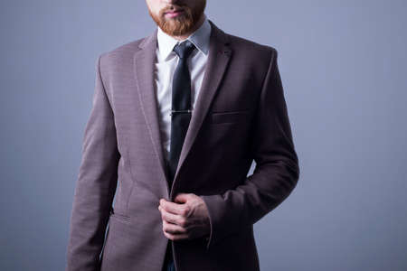studio portrait of a young bearded handsome guy of twenty-five years old, in an official suit, buttoning a button in a jacket. On a dark background. Dramatic light. Official style. Office Style. Fashion and office Foto de archivo