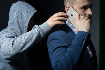 Zaporozhye. Ukraine. February 2020. Close-up portrait of a young bearded guy in a business suit holding an iPhone XS max. A robber in a dark hood, trying to steal a smartphone from behind. New smartphone from Apple. Modern technologies in business. Busine Editorial
