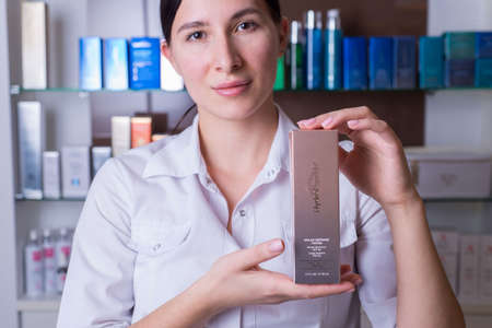 Zaporozhye. Ukraine January 2020. Beauty Salon Prima Vera. The girl is a beautician in defocus, keeps in focus a cosmetic means for body care, firm hydra peptide. Cosmetics in the background