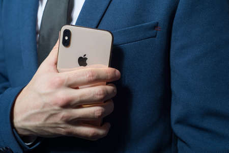 Zaporozhye. Ukraine. February 2020. Close-up portrait of a young bearded guy in a business suit holding an iPhone XS in his hand. New smartphone from Apple. Modern technologies in business. Businessman talking on a new smartphone from Apple. The importanc