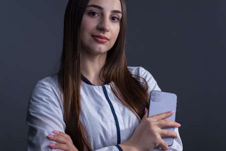 Zaporozhye. Ukraine. February 2020. Studio portrait of a girl in a white coat. The doctor holds in his hand an iPhone 11 from epl. On a gray background. Medical concept for doctors using new Apple services. Use of products of the company epll in medicine.