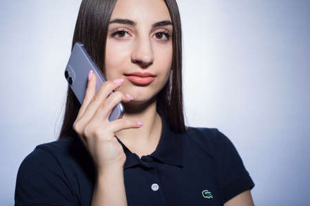 Zaporozhye. Ukraine. February 2020. Studio portrait of a girl of twenty-two years old, in a blue Lacoste polo shirt, holding a new Apple smartphone, iPhone 11. On a white background. Modern technology and the young generation of people. Girl holds a new i