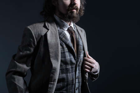 studio dramatic of a young bearded and curly haired guy of thirty years, in an expensive business suit, holds his hand by the lapel of his jacket. On a dark background. Creative man portrait. Advertising of mens jackets, formal suits. Rembrandt Light. free space. Dramatic movie photography. Old mans image. a man with long hair. Beige jacket, checkered vest. White shirt. Designer tie. expressive portrait. Angry man. Looks emotionally at the camera. Charity.