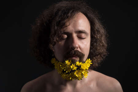 Studio dramatic portrait of a young guy of thirty years old, with his eyes closed. yellow flowers are woven into curly hair and a long beard. Concept of spring flowers in a beard. Flowers and spring.