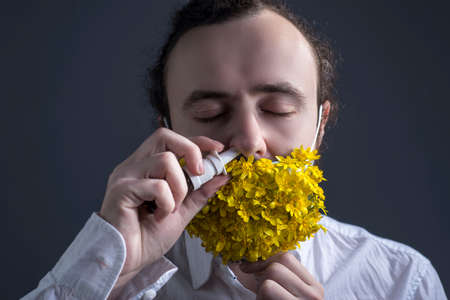 Studio portrait of a young sick guy who takes off a medical mask with yellow flowers to drip nose drops from an allergy to pollen. On a gray background. Medical spring allergic disease concept