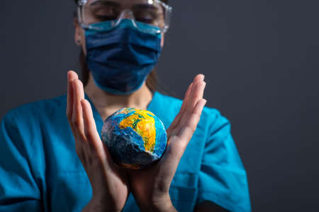 close-up portrait of a girl doctor, in a protective suit, mask and glasses, holds in his hands a model of a small planet Earth. Studio photo on a gray background. coronavirus, covide 19