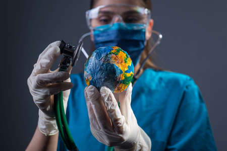 Closeup portrait of a female doctor in a protective mask, gloves, glasses, using a phonendoscope, auscultates the model of planet Earth. coronavirus, covide 19