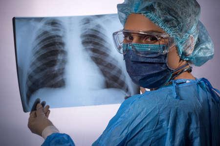 coronavirus pneumonia, Covid 19. A doctor in protective medical clothing examines an X ray of a patient with coronavirus pneumonia. Stock Photo
