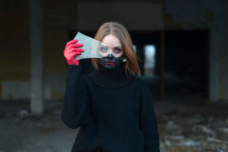beauty portrait of a beautiful girl in a black mask with rhinestones, cool designer makeup. The girl is crying emotionally, holding a broken glass in her hand. coronavirus, covide 19 Stock Photo