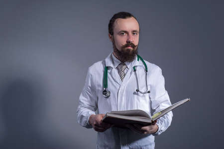 Portrait of a bearded doctor in a white coat and a phonendoscope holding educational books in his hands. Studio photo on a gray background.