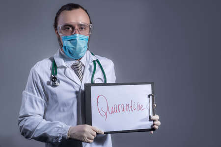 coronavirus. Kovid 19. Portrait of a doctor, in protective clothing and a mask, holding a sheet with the words STOP in his hands. Studio photo on a gray background.