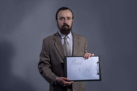 Portrait of a man of thirty, in a business suit, is holding a table with the inscription need job. Studio photo on a gray background.
