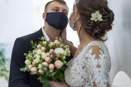 coronavirus infection 2020. Kovid 19. Portrait of a masked bride and groom during a wedding ceremony. Oudoor. Weddings during the period of quarantine and pandemic of coronavirus infection Stock Photo