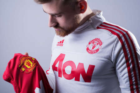Zaporozhye, Ukraine. January 2020. Studio Portrait of a young bearded athlete guy in a sports jacket by Adidas, Manchester United. Football uniform. Football fan