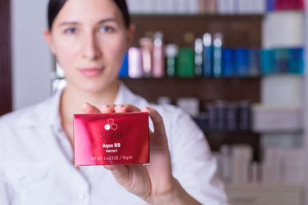 Zaporozhye. Ukraine January 2020. Beauty Salon Prima Vera. Girl beautician in defocus, keeps in focus cosmetic means for body care, company 3Lab In the background cosmetic products