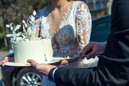 hands of bride and groom cut of a slice of a wedding cake Close up of bride and groom cut a beautiful wedding cake. Outdoor. Beautiful white pastry wedding cake cut by the bride and groom, wedding ceremony. Bride and groom cake