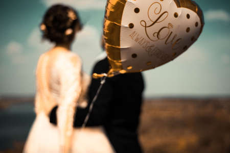 bride and groom, standing with their backs, cuddling in defocus blur, holding a gel ball, with the inscription Love Forever, against the backdrop of a river landscape. Rustic style wedding photography. Happy twenty-five years old bride and groom couple in love, standing with their backs holding an balloon with the inscription