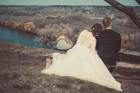 Runaway Bride. Wedding. Groom catches his bride. loving couple of bride and groom, hugging, sitting on a bench, looking into the distance, against the backdrop of a village landscape, a river. Happy wedding day. twenty-five years old romantic shooting of a bride and groom