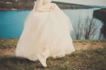 Zaporozhye. Ukraine. April 2020. Portrait of a bride in Nike sports sneakers, against a natural background. In creative artistic tinting funny young bride wearing sporting shoes puts on a garter and smiles
