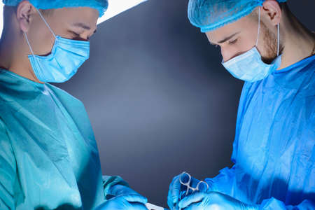 close-up portrait of two surgeons operating in an operating room with instruments. In sterile medical surgical special clothing and masks. Surgery of internal organs, reconstructive and plastic surgery. Medical concept of minimalism