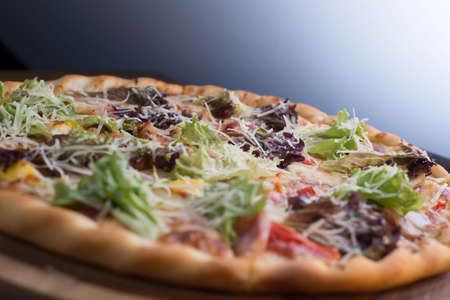 Thinly sliced pepperoni is a popular pizza topping in American-style pizzerias closeup pizza on a tray, with vegetables and meat, in a rustic style. Unusual angle. Salad, vegetable pizza, meat lunch. Friendly pizza. The texture of the pizza. Food. Bad food. Carbohydrate food Stock Photo