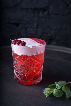 Cosmopolitan cocktail in nice red color in front of a black background promotional shot of a red alcoholic cocktail for parties. With a green sprig of mint and decorative raspberries. On a dark background. in a rustic style. Alcohol. Non-alcoholic fruit drink, with natural ingredients, with ice, a sprig of mint