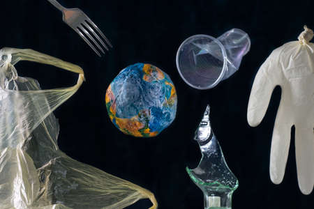 The concept of planet Earth pollution by plastic, metal, polyethylene, glass, rubber, smoke. Around the model of planet Earth, against the background of space, a rubber medical glove levitates, resembles a person, a steel fork, a plastic bag, a crumpled plastic glass, a broken glass bottle. On a black background. Minimalistic concept of environmental pollution by air emissions, smoke pollution, destruction of the planet by industrial waste. Global warming Stock Photo