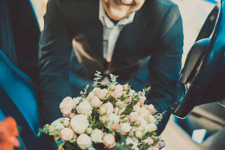 close up of wedding bouquet Portrait of a smiling groom of twenty-five years old, pulls out a bouquet of flowers from a car. Wedding preparation of the groom for the ceremony. In creative art toning