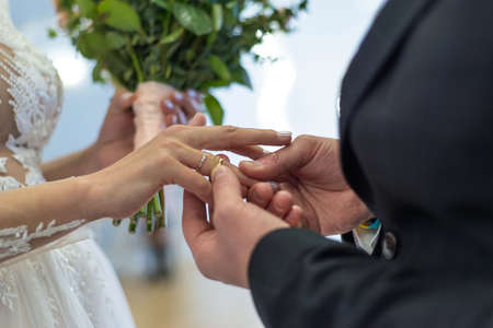 Close up on hand of a man put on an engagement ring on the finger of the bride Close-up hands of a bride and groom exchanging wedding rings on a wedding day. Wedding ceremony.
