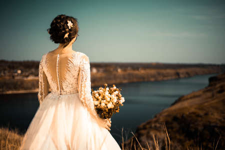 general plan portrait from the back of a young bride, standing with a wedding bouquet, looking into the distance of a landscape with a river. Creative art tinting. Wedding photo of a young beautiful bride of twenty-five years, waiting for the holiday. Single bride Stock Photo