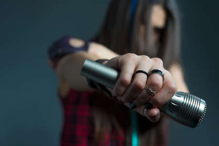 Closeup portrait of a beautiful girl holding a microphone in her hand. Studio photo on a gray background. portrait of a young beautiful girl of twenty-seven years old, with red lipstick, holding a microphone in her hand, with tousled hair sings rock and roll music emotionally and aggressively. Hard Rock. Metal music, heavy metal.