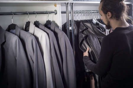 Portrait of a young bearded millennial guy. In a men's clothing store, a guy in the middle of a counter with business jackets selects a leather brutal rock and roll jacket, referring to a free dress code Stock Photo
